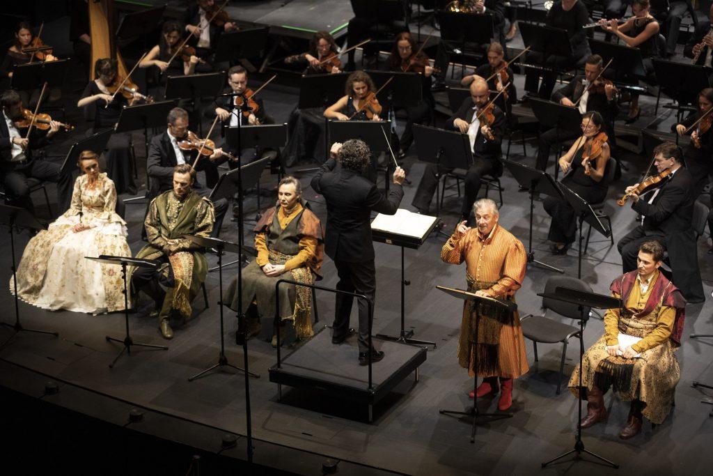 Widok z góry. Od lewej siedzi solistka w jasnej sukni i czterech solistów w kostiumach szlacheckich. Między nimi dyrygent. Za solistami widoczna część grupy smyczkowej orkiestry.