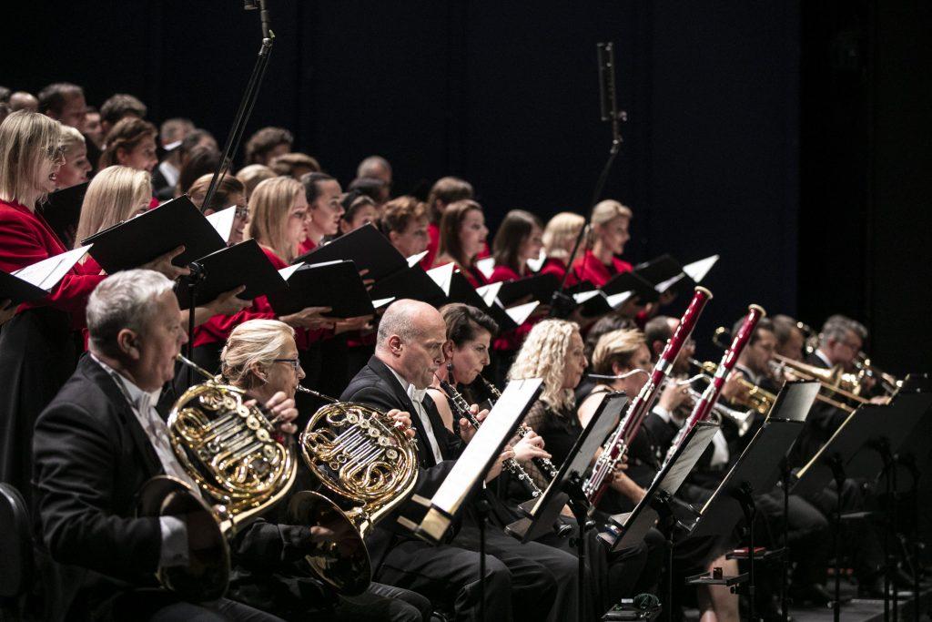 Zbliżenie na część orkiestry i chóru opery. W pierwszym rzędzie siedzą muzycy grupy dętej-blaszanej ( waltornie, puzony) i drewnianej ( oboje, fagoty). Za nimi Chór Opery i Filharmonii Podlaskiej. Trzymają w rękach otwarte teczki z nutami.