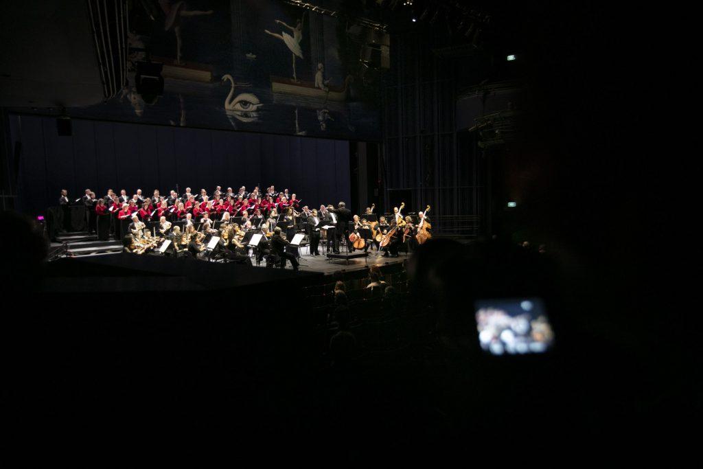 Na widowni półmrok. Zdjęcie zrobione z boku. Na scenie gra orkiestra Opery i Filharmonii Podlaskiej. Za nimi stoi chór mieszany, mężczyźni w czarnych frakach, kobiety w czerwonych żakietach.