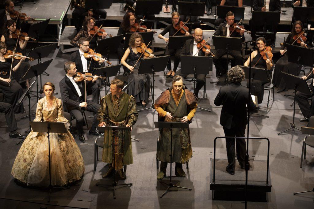 Na scenie troje solistów , kobieta w jasnej sukni i dwóch mężczyzn w kostiumach szlacheckich. Obok dyrygent. Za nimi widoczna część grupy smyczkowej Orkiestry Opery i Filharmonii Podlaskiej.
