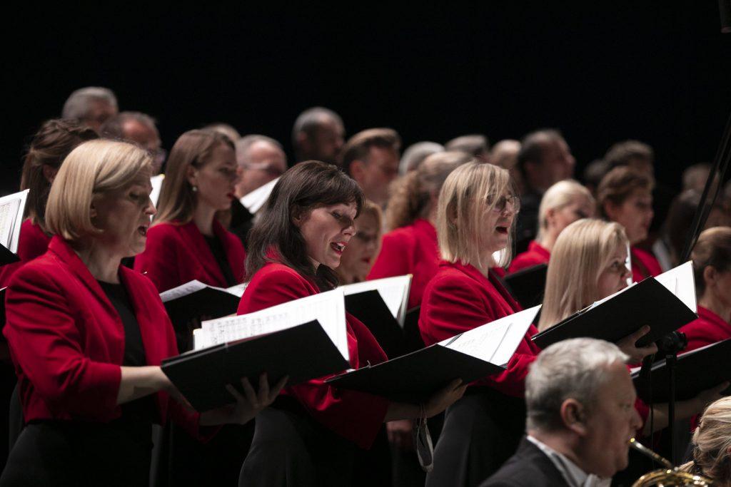 Zbliżenie na Chór Opery i Filharmonii Podlaskiej podczas wykonywania utworu. Panie w czerwonych żakietach trzymają otwarte teczki z nutami.