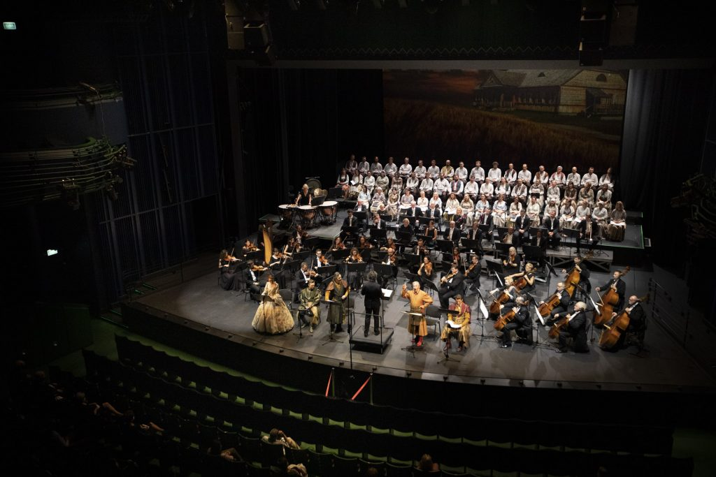 Widok sceny z góry. Z przodu soliści w kostiumach i dyrygent. Za nimi orkiestra. Na końcu sceny siedzi chór w białych kostiumach.
