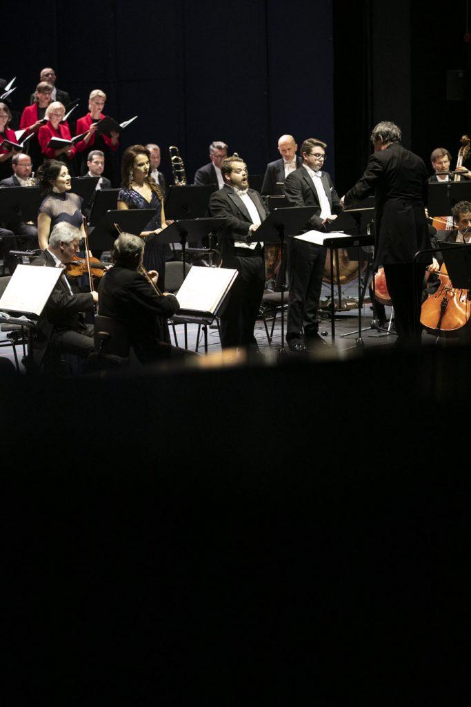 Na środku stoi czterech solistów, dwie kobiety w eleganckich sukniach i dwóch mężczyzn we frakach. Przed nimi stoi dyrygent. Po obydwu stronach widać część grupy smyczkowej orkiestry. Za nimi po lewej stronie widać część chóru.