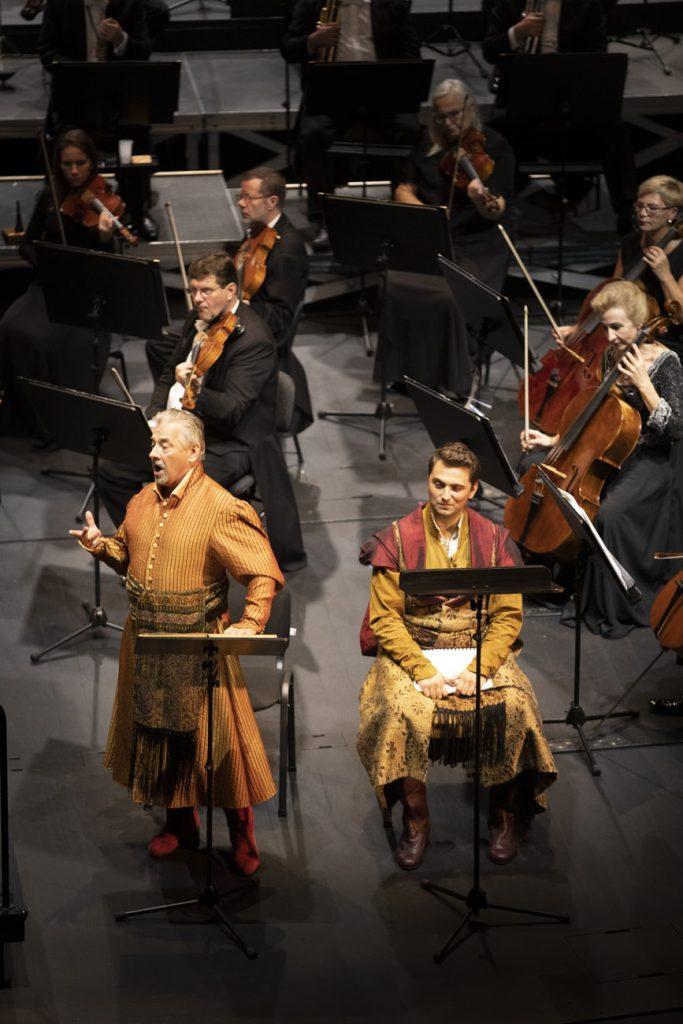 Z przodu dwóch solistów w kostiumach szlacheckich, za nimi widoczna część grupy smyczkowej orkiestra.