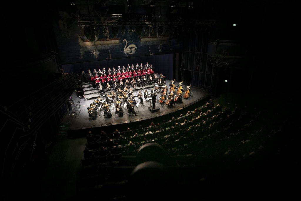 Scena i widownia Opery i Filharmonii Podlaskiej. Widok z balkonu. Na scenie orkiestra z dyrygentem. Za nimi stoi chór mieszany. Na widowni publiczność siedząca na co drugim krześle.