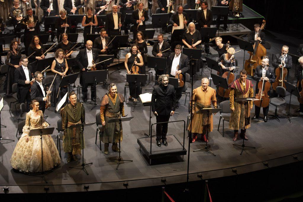 Na scenie stoją artyści spektaklu ''Verbum Nobile'' w kostiumach oraz dyrygent. Za nimi orkiestra.