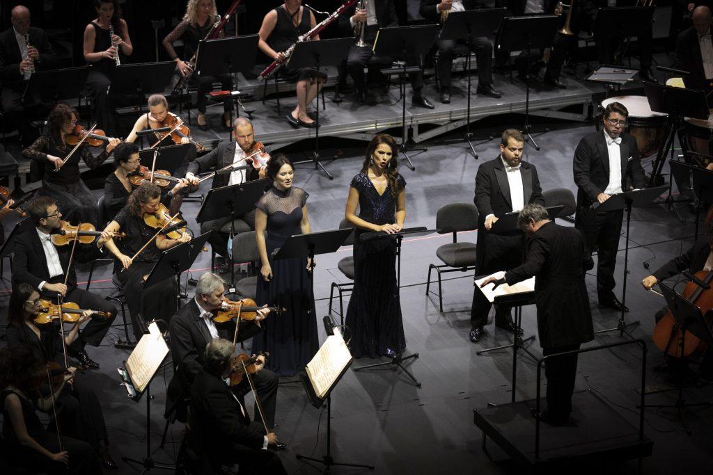 Na środku stoi czworo solistów, dwie kobiety w długich sukniach i dwóch mężczyzn we frakach. Przed nimi stoi dyrygent. Po lewej stronie siedzi część grupy smyczkowej. Za nimi siedzi część grupy dętej.