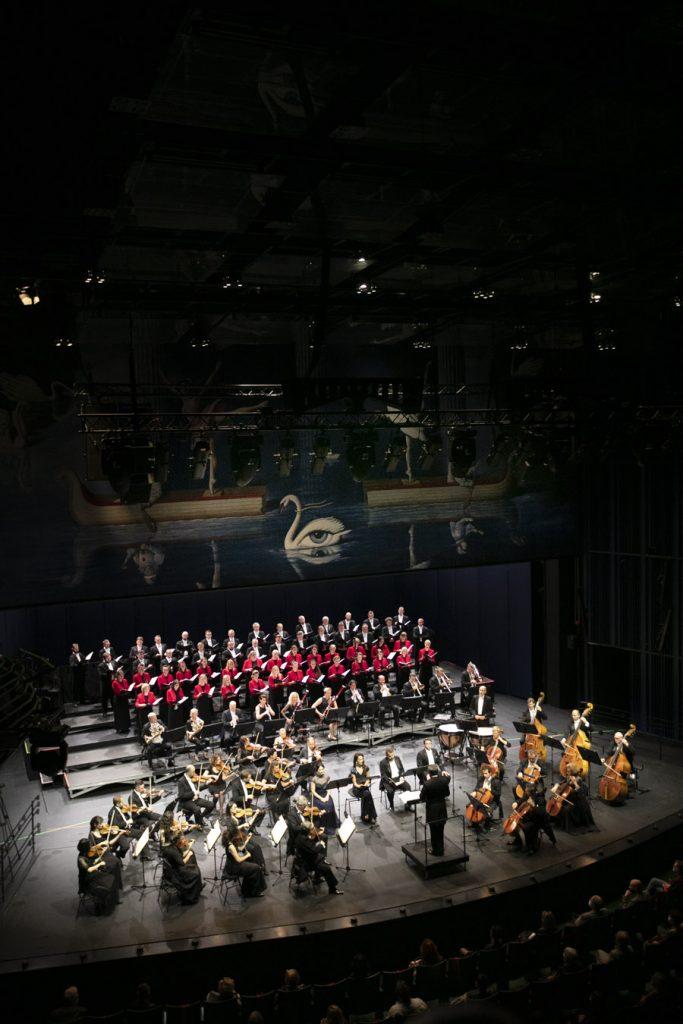 Zdjęcie zrobione z góry. Na scenie siedzi czworo solistów, dookoła nich siedzą muzycy sekcji smyczkowej orkiestry. Za nimi w rzędzie siedzi sekcja dęta. Na końcu stoi w kilku rzędach chór mieszany. Z przodu stoi dyrygent.
