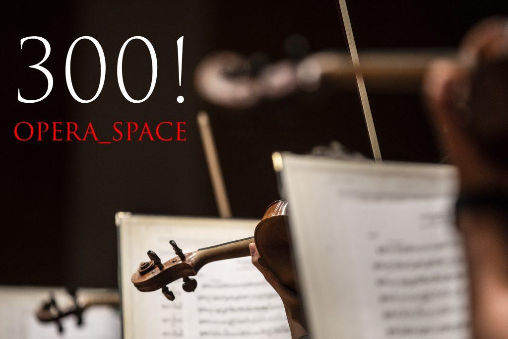 Widok nut na pulpitach. Pomiędzy nimi widoczne główki skrzypiec. Po lewej stronie napis: 300! Opera_space.