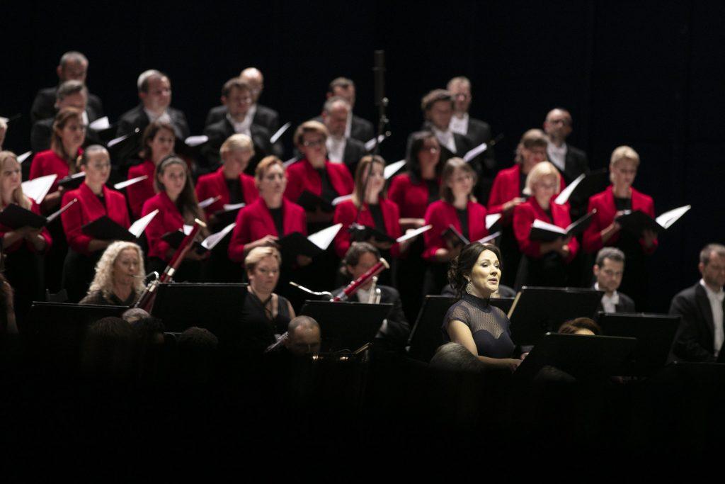 Na środku stoi solistka w ciemnej sukni, za nią siedzi grupa instrumentów dętych. Za muzykami, w kilku rzędach stoją artyści chóru mieszanego.
