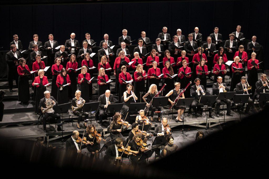 Zbliżenie na część orkiestry, po lewej stronie grupa smyczkowa , za nimi w rzędzie siedzi grupa dęta. Dalej, w kilku rzędach stoi chór mieszany.