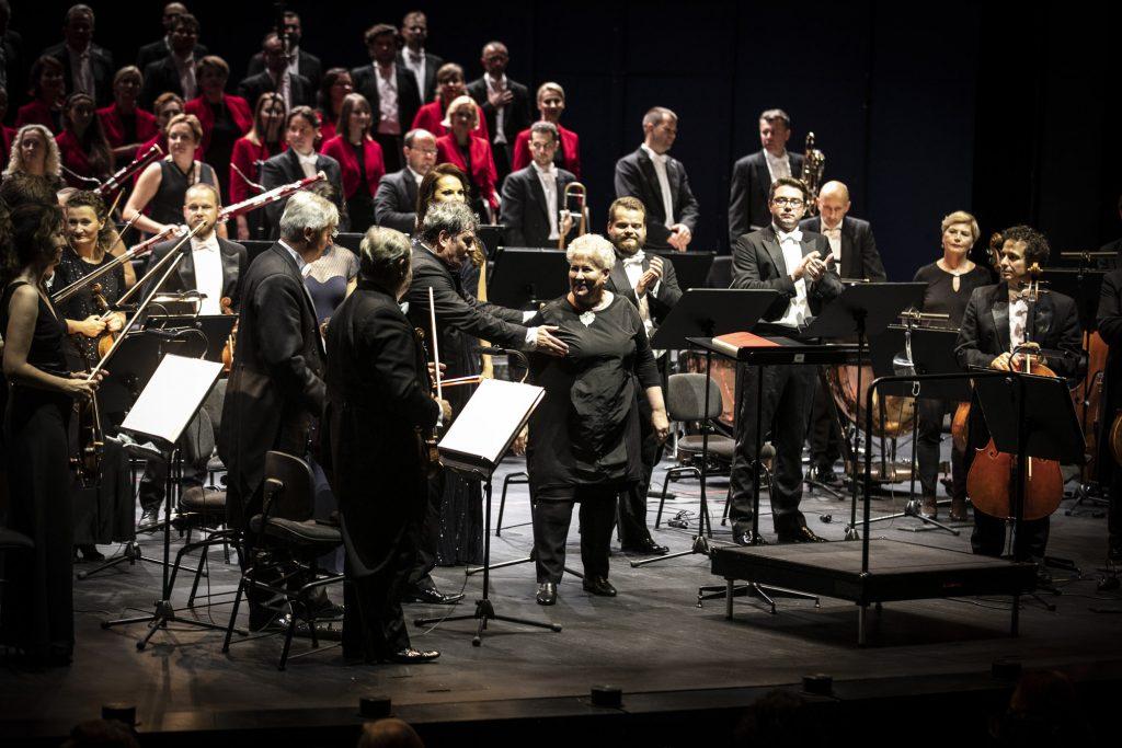 Na scenie część Chóru i Orkiestry Opery i Filharmonii Podlaskiej. Wszyscy stoją. Na środku Prof. Violetta Bielecka, kierownik artystyczny chóru oraz Mirosław Błaszczyk, dyrygent.