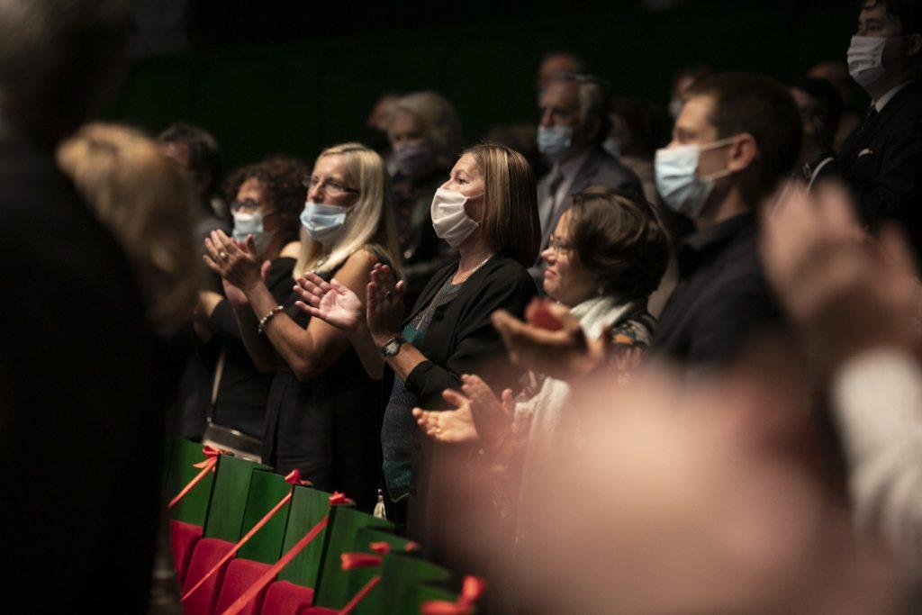Publiczność Opery i Filharmonii Podlaskiej na stojąco oklaskuje artystów. Wszyscy mają na twarzach maseczki ochronne.