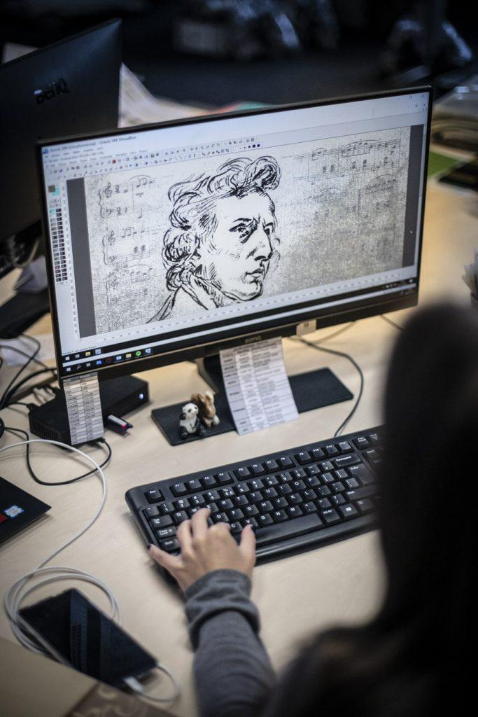 Na zdjęciu monitor komputera. Na nim wyświetlona twarz Chopina, część szkicu z dywanu promującego koncerty w Operze.