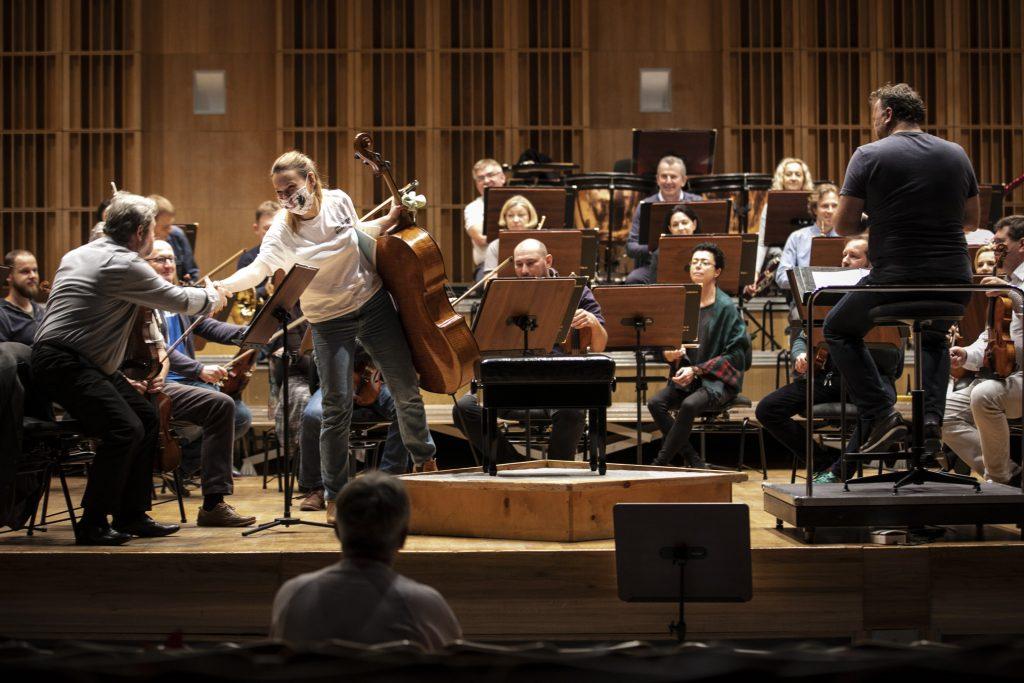 Na scenie siedzi orkiestra. Solistka trzymająca wiolonczelę, podaje rękę mężczyźnie grającym na skrzypcach.