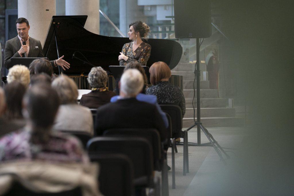 Na krzesłach, na dolnym foyer siedzi kilkanaście osób. Przed nimi dwójka solistów, mężczyzna mówiący do mikrofonu oraz kobieta patrząca w jego kierunku.