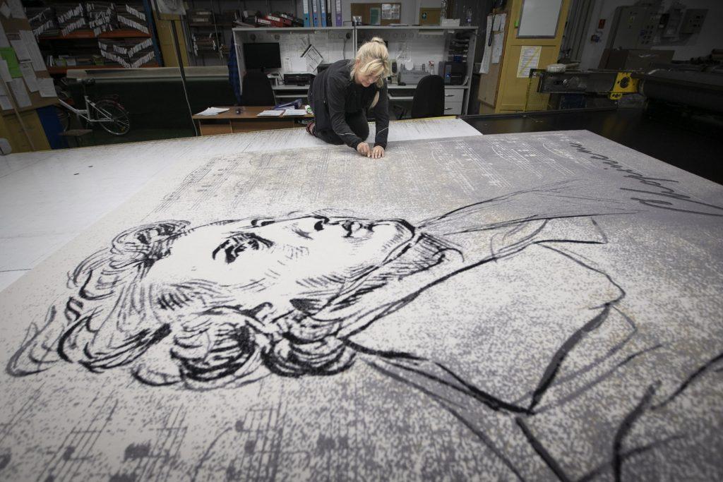 Na dużym stole leży szary dywan z wizerunkiem Chopina promujący cykl koncertów w Operze. Obok pochylona nad nim, klęczy kobieta.