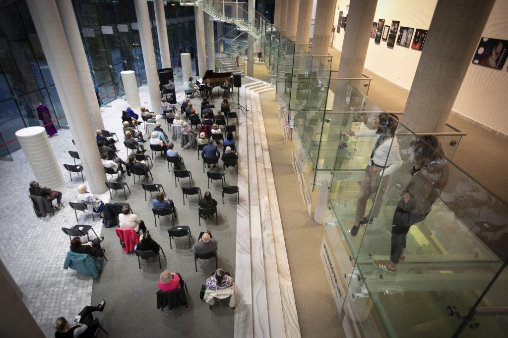 Widok z góry. Na dolnym foyer trwa koncert z okazji Międzynarodowego Dnia Muzyki. Na krzesłach siedzą widzowie. Przed nimi siedzi dwójka solistów, kobieta i mężczyzna. Obok kobieta grająca na fortepianie.