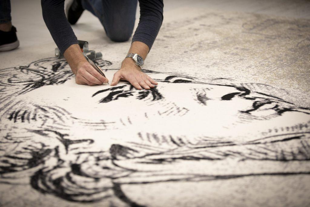Na zdjęciu widać część dywanu z wizerunkiem Chopina. Na nim klęczy mężczyzna szkicując coś na wysokości twarzy.
