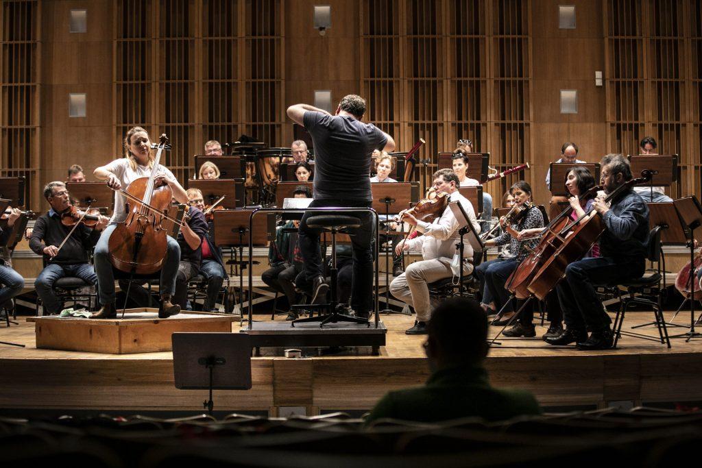 Na scenie, podczas próby do koncertu, gra orkiestra. Przed nimi solistka grająca na wiolonczeli. Po prawej stronie stoi dyrygent.