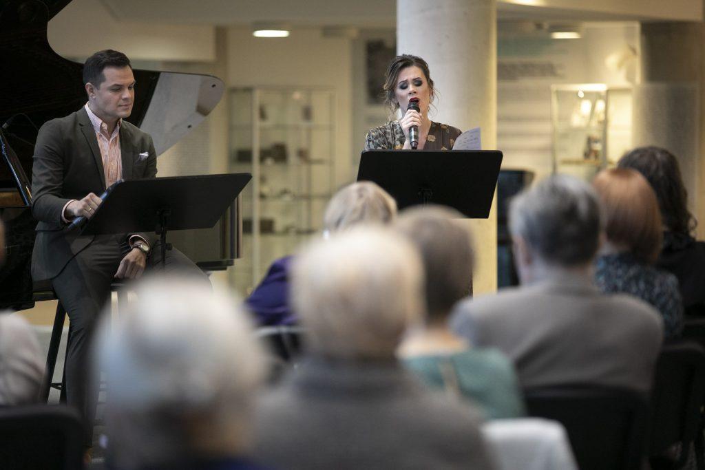 Dwójka solistów, kobieta i mężczyzna, siedzą na wysokich krzesłach na foyer. Kobieta śpiewa do mikrofonu. Przed nimi siedzi publiczność.