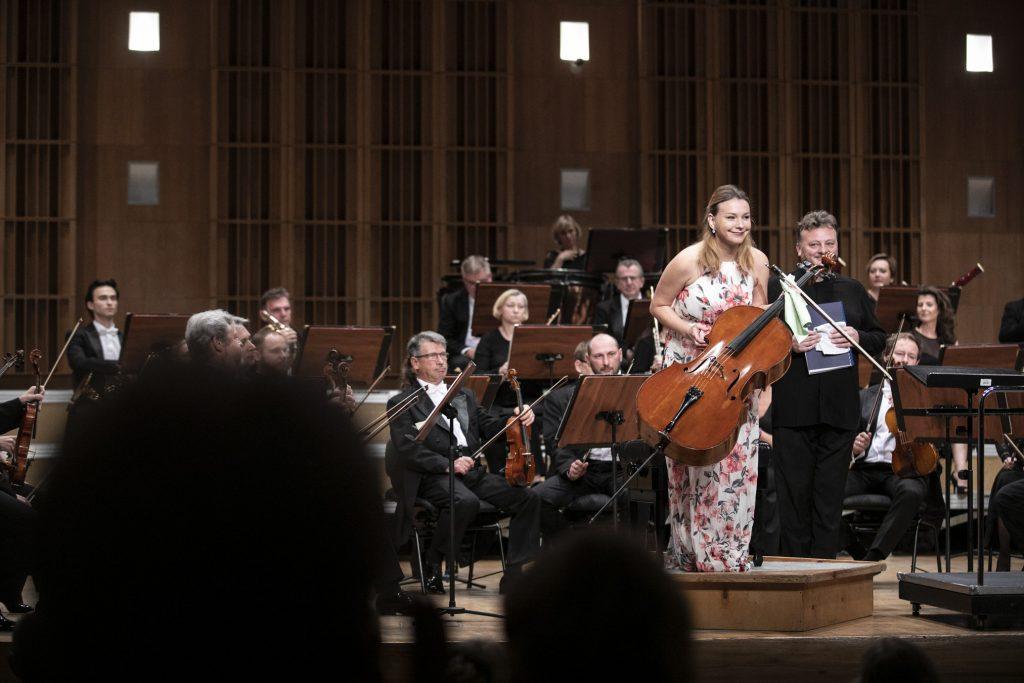 Na podeście stoi kłaniając się solistka trzymająca wiolonczelę. Za nią siedzi orkiestra.