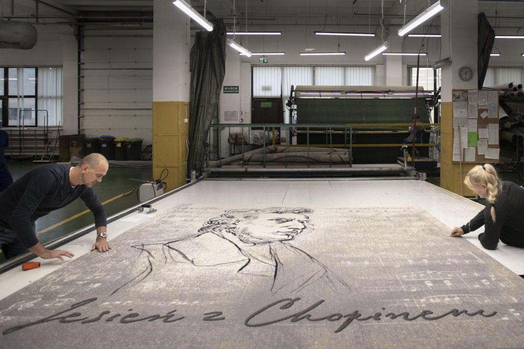Na środku rozłożony jest duży dywan z wizerunkiem Chopina, promujący cykl koncertów w Operze. Po obydwu stronach pochylone nad nim dwie osoby.