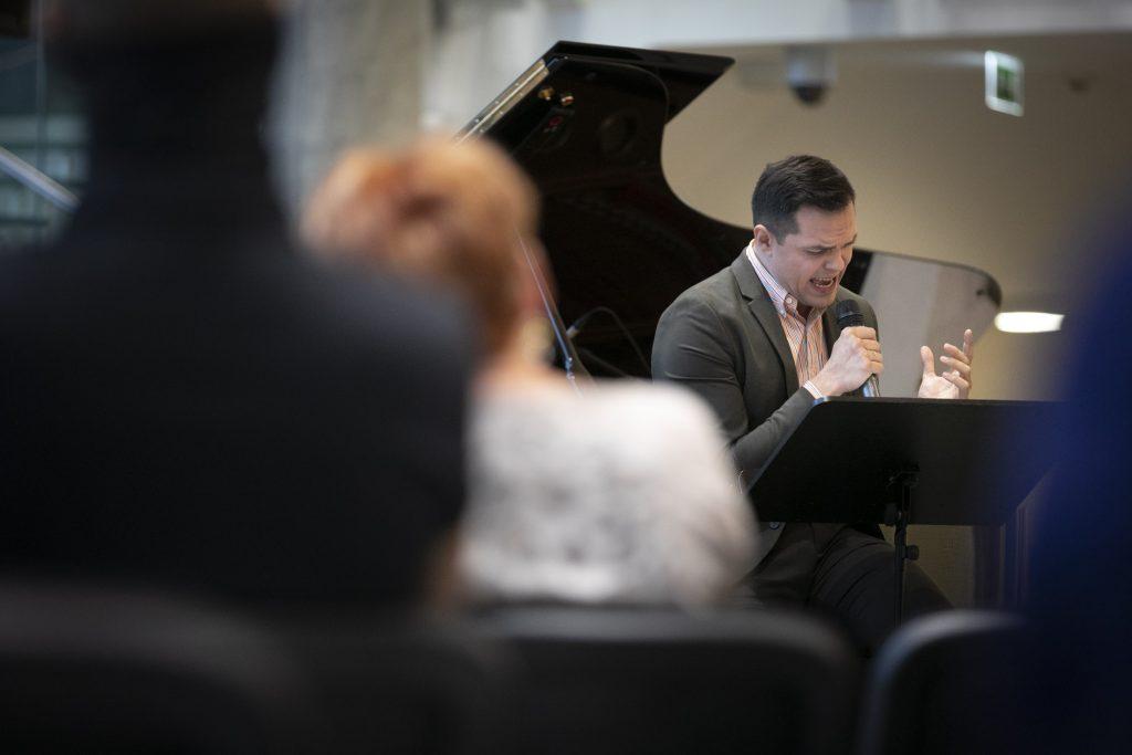 Mężczyzna siedzący przed pulpitem, śpiewa do mikrofonu. Za nim stoi fortepian.
