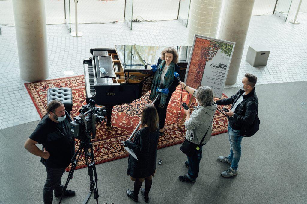 Zdjęcie zrobione z góry.Dolne foyer. Przy fortepianie stoi Dyrektor Opery i Filharmonii Podlaskiej. Obok , z mikrofonami wyciągniętymi w jej stronę stoją fotoreporterzy. Wszyscy mają na twarzach maseczki ochronne.