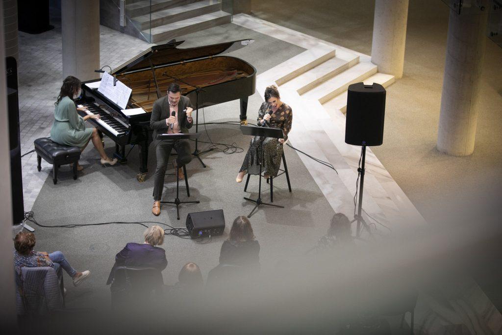 Dolne foyer. Na fortepianie gra kobieta w zielonej sukience. Obok, na wysokich krzesłach siedzą soliści. Kobieta i mężczyzna. Śpiewają. Przed nimi na krzesłach siedzi publiczność.