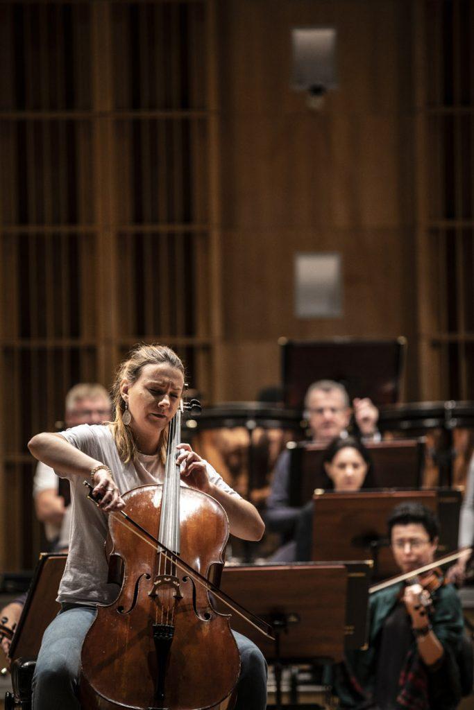 Kobieta grająca na wiolonczeli podczas próby. Za nią orkiestra.