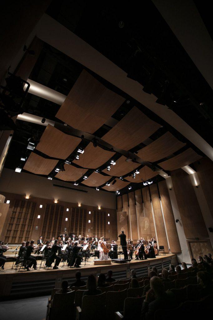 Zdjęcie zrobione z oddali na scenę. Na niej podczas koncertu Orkiestra Opery i Filharmonii Podlaskiej. Na środku siedzi wiolonczelistka, po jej lewej stronie stoi dyrygent. Widownia w półmroku.
