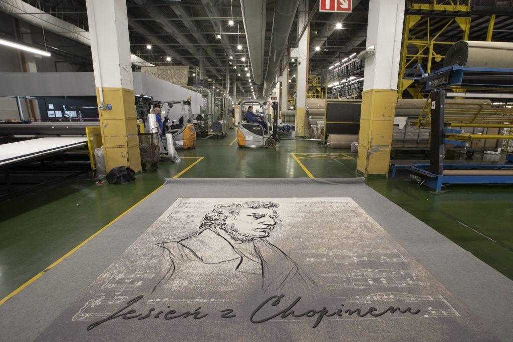 Na podłodze, na hali produkcyjnej, leży szary, duży dywan, z wizerunkiem Chopina, promujący cykl koncertów w Operze. Dalej , w wózku widłowym siedzi mężczyzna. Po bokach maszyny i bele wykładzin.