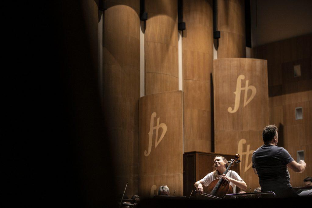 Kobieta grająca na wiolonczeli podczas próby. Obok niej stoi dyrygent.