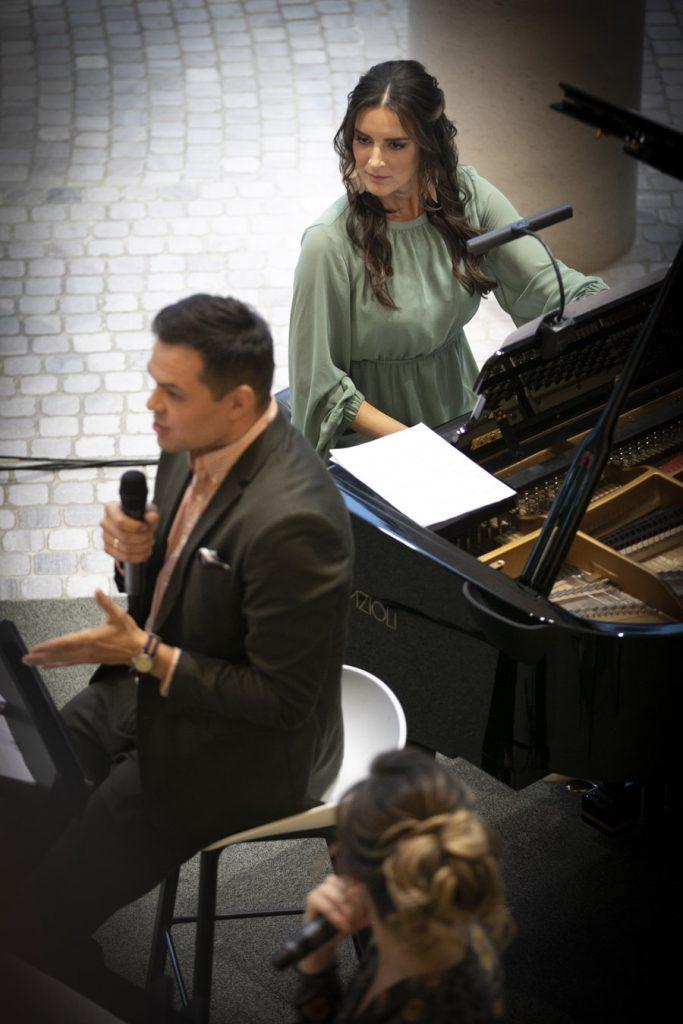 Przy fortepianie siedzi kobieta w zielonej sukience. Obok siedzą soliści. Mężczyzna mówiący do mikrofonu, dalej kobieta trzymająca mikrofon.