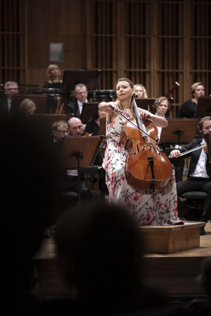 Na podeście, podczas koncertu, siedzi solistka grająca na wiolonczeli. Za nią orkiestra.