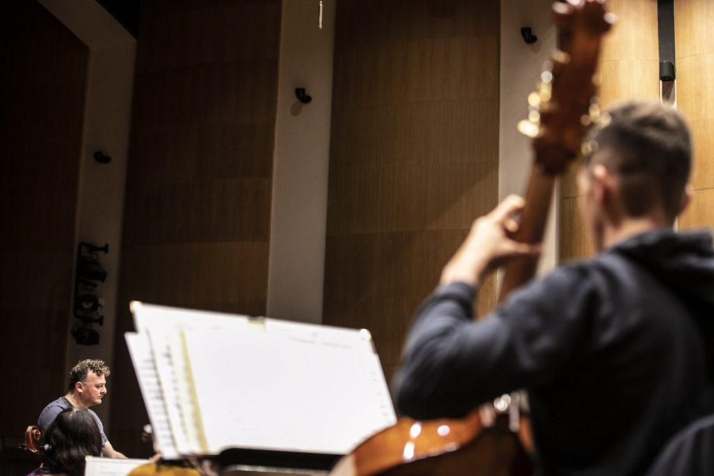 Po prawej stronie przed pulpitem z nutami, siedzi mężczyzna grający na kontrabasie. Po lewej stronie, w oddali siedzi dyrygent.