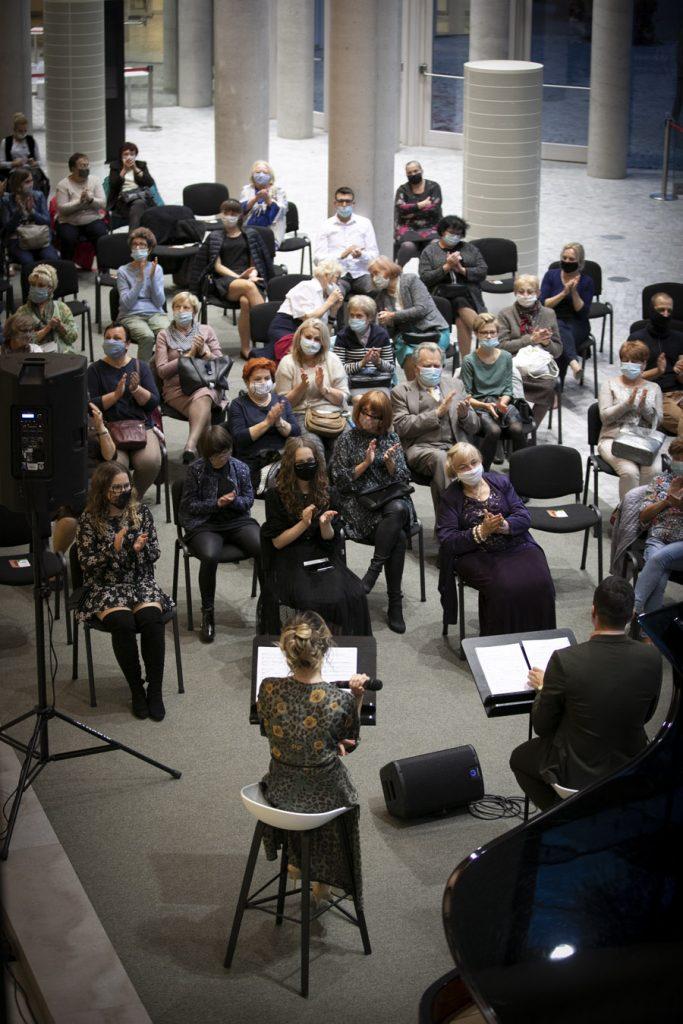 Dolne foyer. Koncert z okazji Międzynarodowego Dnia Muzyki. Na krzesłach, w maseczkach ochronnych siedzi publiczność. Przed nimi siedzą soliści.