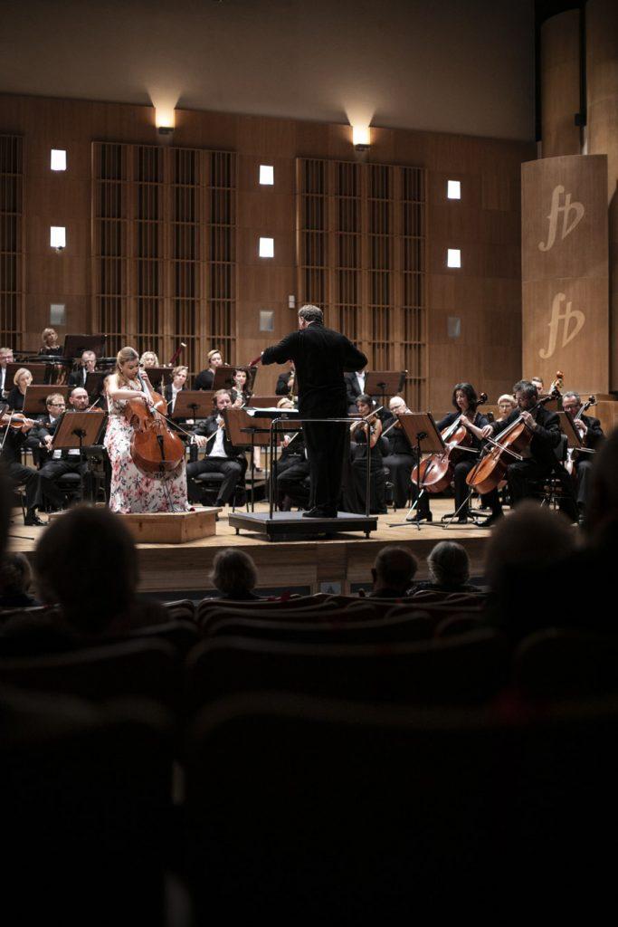 Widok z oddali na scenę na której grają muzycy Orkiestry Opery i Filharmonii Podlaskiej. Na środku , na podeście stoi dyrygent. Po jego lewej stronie siedzi wiolonczelistka. Na widowni w półmroku widać kilka osób.