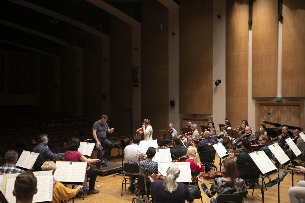 Próba do koncertu. Przy pulpitach, na których rozłożone są nuty, siedzi orkiestra Opery. Na środku siedzi dyrygent.