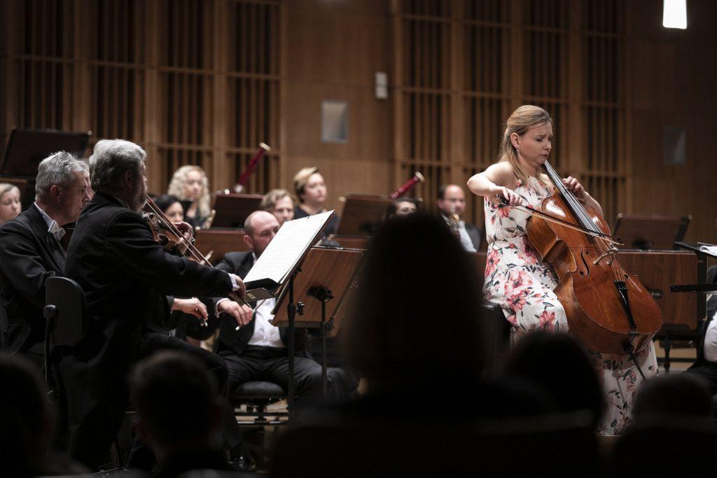 Na scenie gra orkiestra Opery. Po prawej stronie kobieta w sukience w kwiaty gra na wiolonczeli.