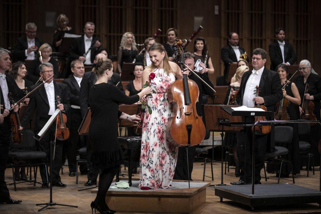 Na scenie stoi orkiestra Opery i Filharmonii Podlaskiej. Na środku w długiej sukni w kwiaty stoi solistka trzymając wiolonczelę. Zwrócona jest w kierunku dziewczyny wręczającej jej czerwoną różę.