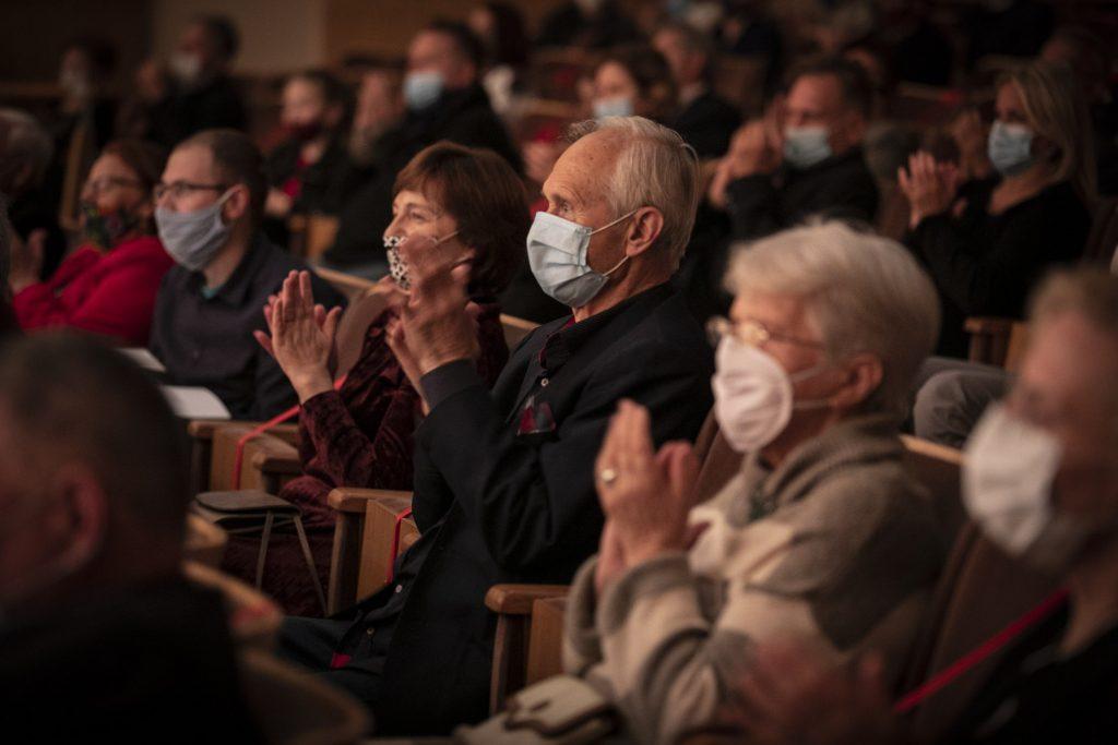 Widownia podczas koncertu oklaskuje artystów. Wszyscy mają na twarzach maseczki ochronne.