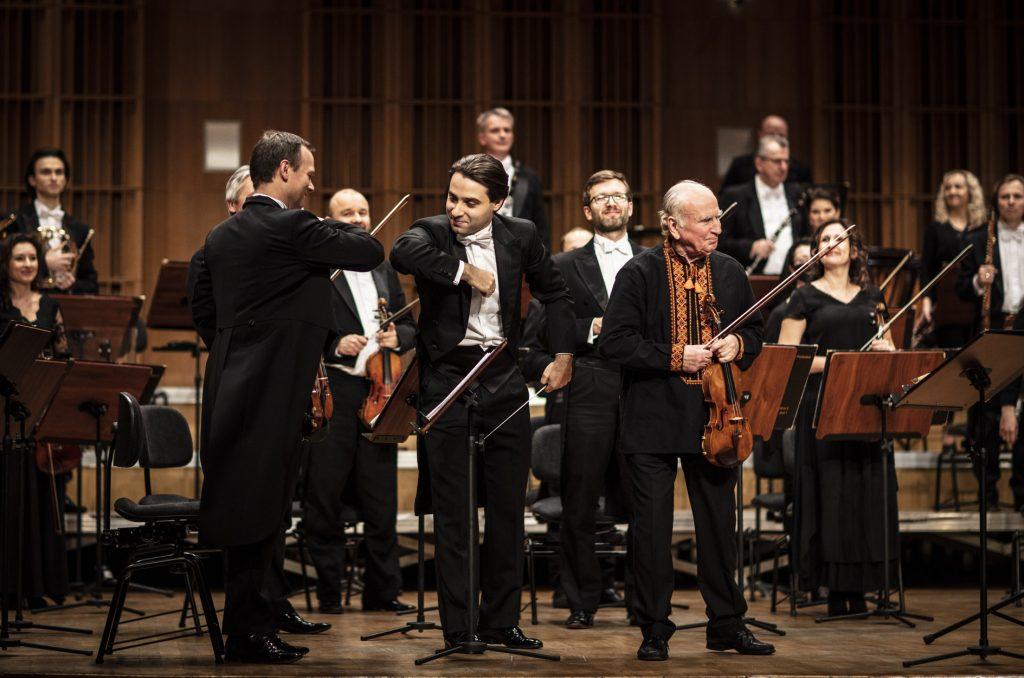 Na scenie z przodu dwóch mężczyzn dotykających się łokciami w geście powitania. Obok stoi mężczyzna trzymający skrzypce. Za nimi stoi orkiestra.