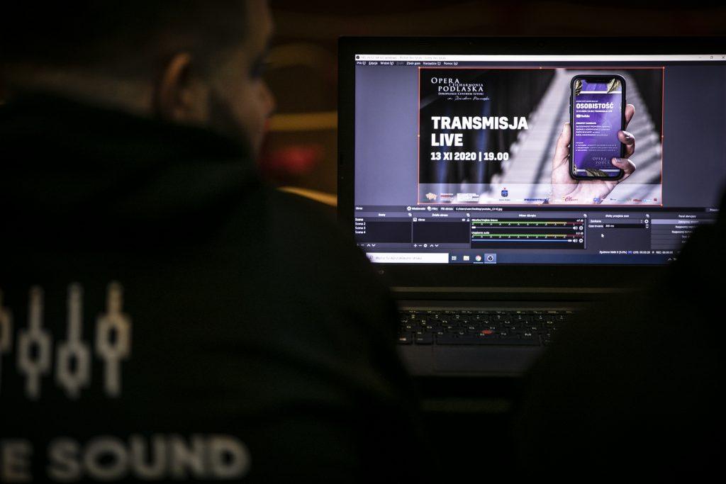 Na zdjęciu widok na monitor. Na nim widać grafikę promującą koncert online 13.11.2020 r. Przed monitorem siedzi mężczyzna.