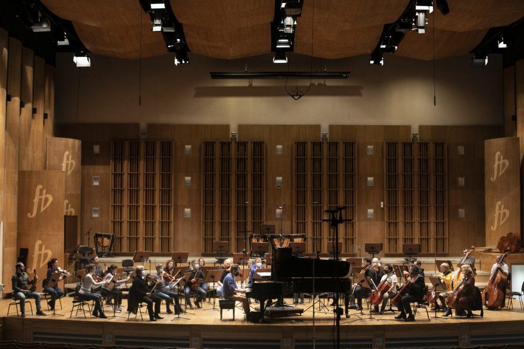 Próba do koncertu. Na scenie siedzi Orkiestra Opery i Filharmonii Podlaskiej. Na środku , przy fortepianie siedzi mężczyzna.