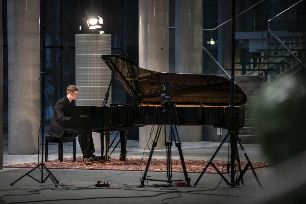 Koncert na foyer. Mężczyzna gra na fortepianie.