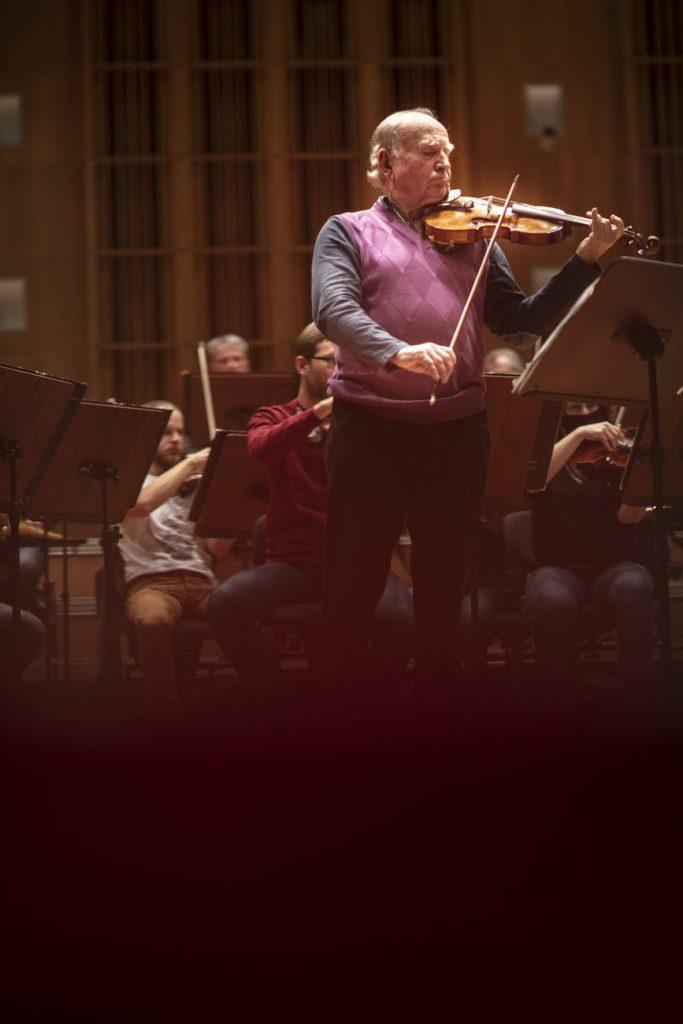 Próba do koncertu. Na środku, na scenie stoi mężczyzna grający na skrzypcach. Za nim siedzi orkiestra.