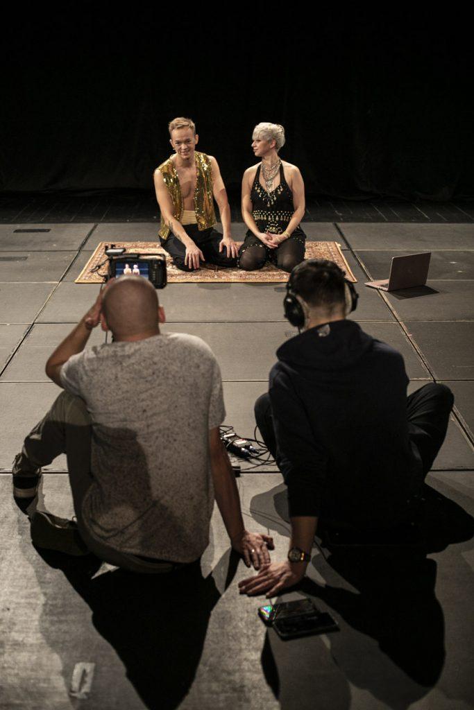 Warsztaty taneczne online. Na scenie, na dywanie siedzą dwie osoby. Kobieta i mężczyzna w strojach indyjskich. Przed nimi siedzą dwaj mężczyźni. Przed jednym z nich stoi kamera na statywie.