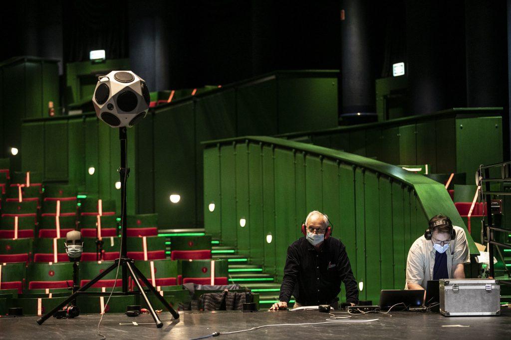 Pomiary akustyczne na dużej scenie Opery i Filharmonii Podlaskiej. Pod sceną, w słuchawkach i maseczkach ochronnych stoi dwóch mężczyzn.